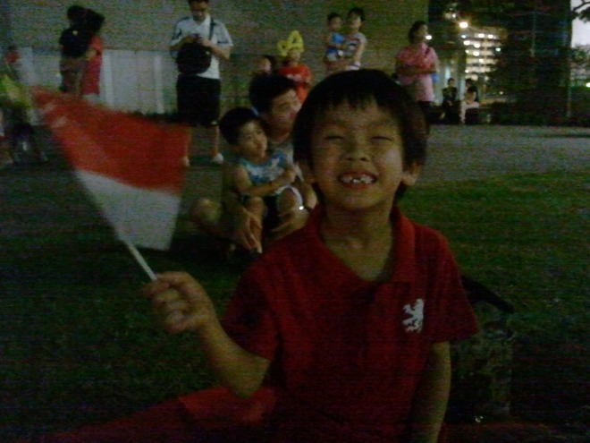 YH with his toothless grin holding the Singapore flag
