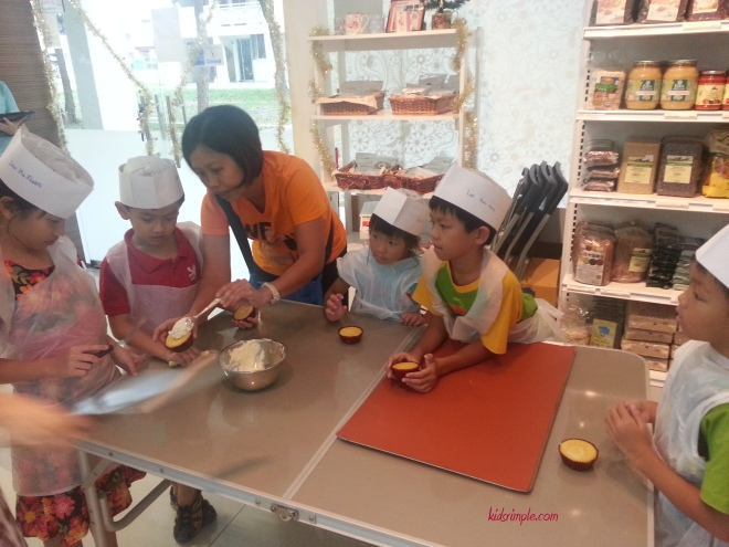 Sengkang Babies' mummy helping the kids to spread the butter cream on the cupcakes. Not easy you know!