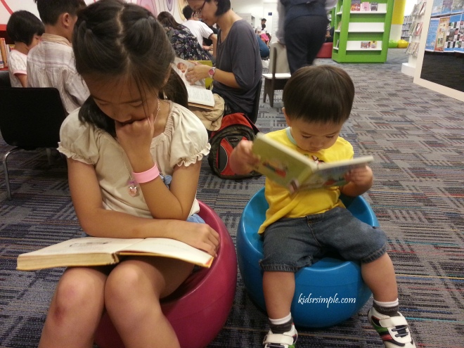 Reading with his sister in the library.